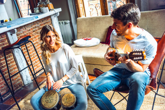 Young happy couple playing music