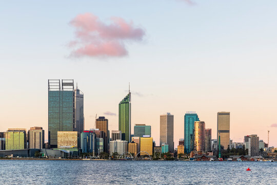 Australia, Perth, Downtown skyscrapers seen across Swan river at sunset