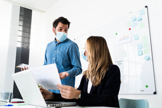 Business people wearing protective masksworking in office