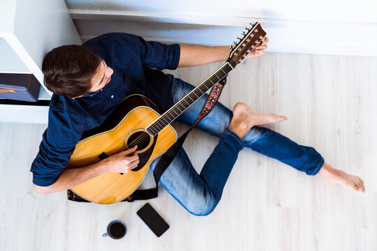 Musician playing acoustic guitar while sitting on floor at studio