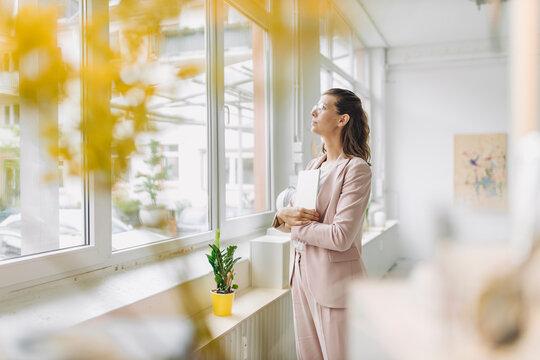 Businesswoman looking through window in office