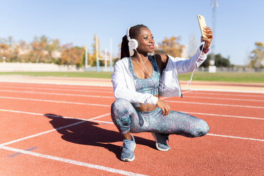 Smiling female athlete taking selfie while listening music on running track during sunny day
