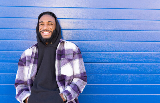 Cheerful young man with hands in pockets against blue corrugated wall