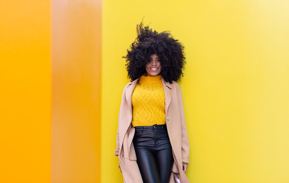 Smiling curly hair woman leaning on yellow wall
