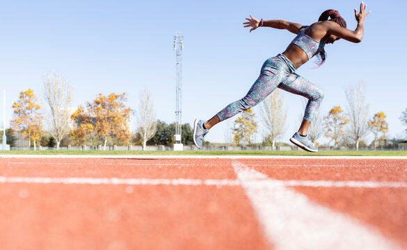 Sportswoman with dedication running on sports track against clear sky during sunny day