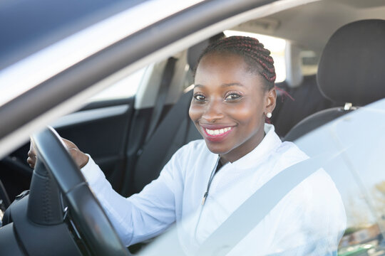 Smiling woman holding steering wheel while sitting in car