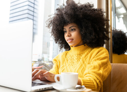 Curly hair woman using laptop while sitting at cafe