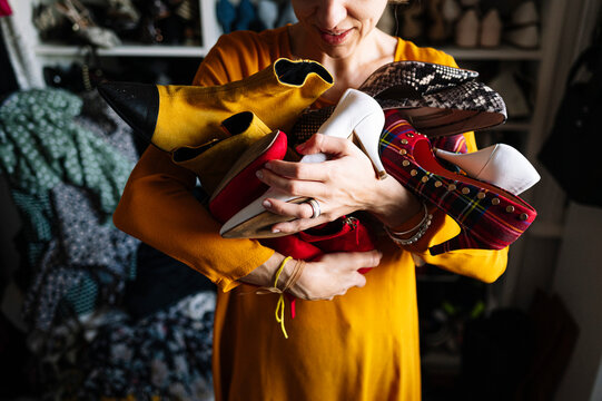 Woman carrying variation of shoes in wardrobe at home