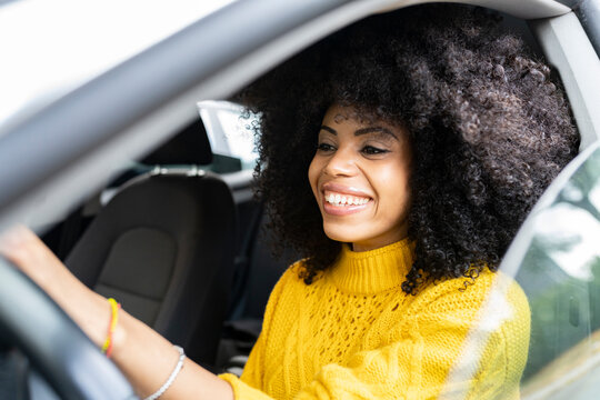 Curly hair woman smiling while driving car