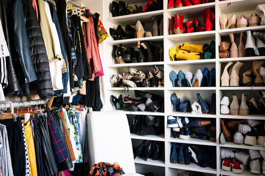 Abundance of footwear and clothes in wardrobe at home