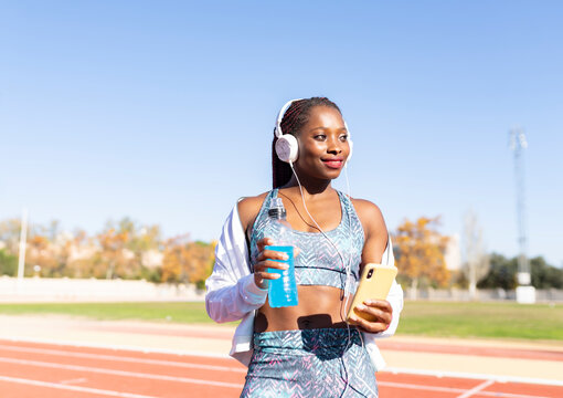 Smiling sportswoman looking away while listening music holding energy drink and smart phone against clear sky