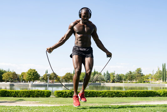 Sportsman doing skipping exercise while listening music through headphones in park on sunny day