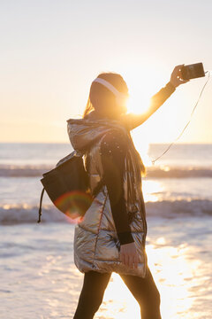 Mid adult woman taking selfie with smart phone against sea during sunset
