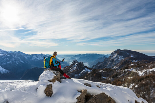 Male hiker using mobile phone while sitting on mountain against sky during winter, Orobic alps, Lecco, Italy