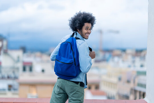 Cheerful young man with blue backpack standing on terrace in city