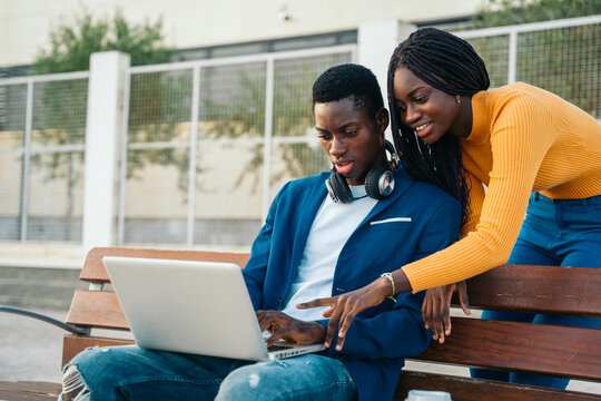 Girlfriend and boyfriend using laptop together on bench