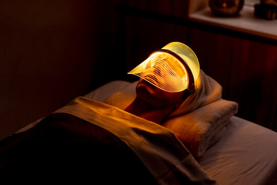 Young woman wearing yellow mask during rejuvenating treatment in dark at beauty spa