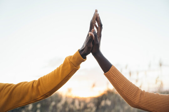 Heterosexual couple touching hands in field during sunset against clear sky