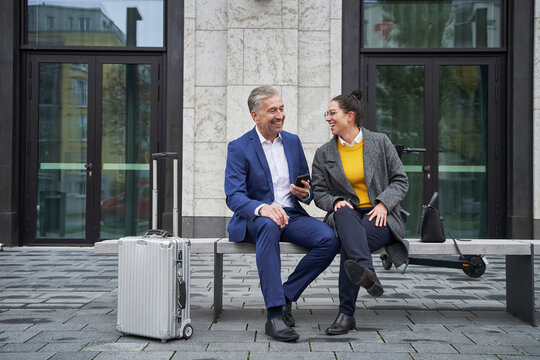 Cheerful male and female professionals talking while sitting on bench against building
