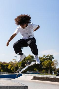 Sportsman skateboarding at skateboard park during sunny day