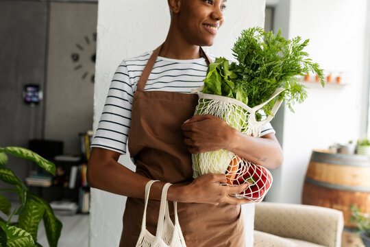 Pretty woman in apron carrying net with fresh vegetables