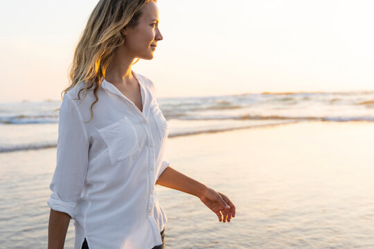 Smiling woman looking away while standing against sea during sunset