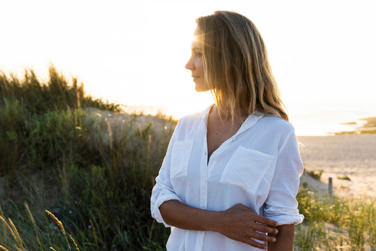 Mid adult woman looking away while standing by sand dune