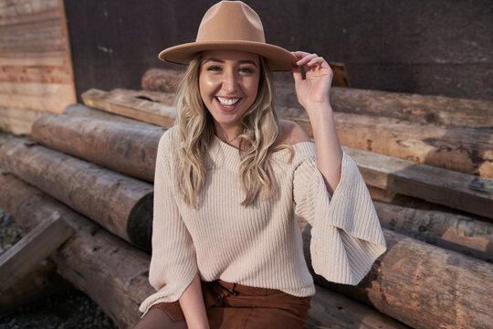 Cheerful beautiful woman wearing hat sitting on woodpile