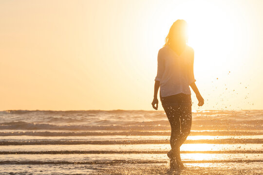 In silhouette of woman splashing water while standing at beach during sunset