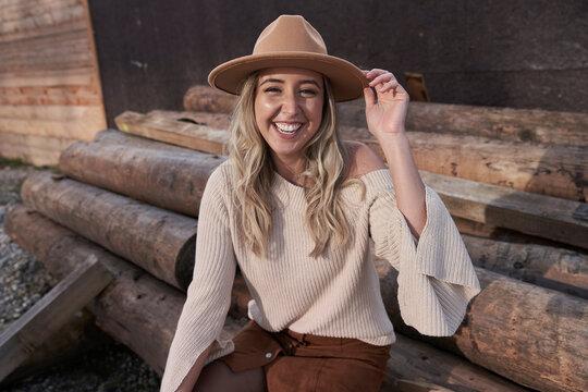 Cheerful beautiful woman wearing hat sitting on logs