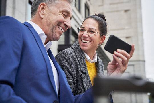 Cheerful businesswoman looking at senior male colleague sharing smart phone