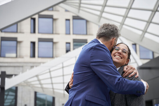 Senior businessman hugging cheerful businesswoman while greeting in city