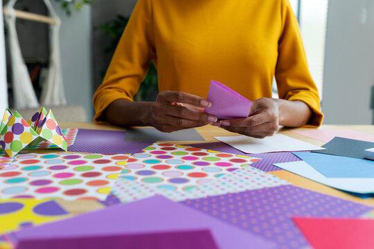 Origami artist sitting in studio folding colorful paper