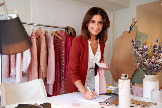 Smiling fashion designer writing in diary while holding fabric swatch at design studio