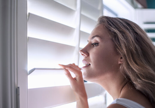 Close-up of beautiful woman looking through window blinds at home