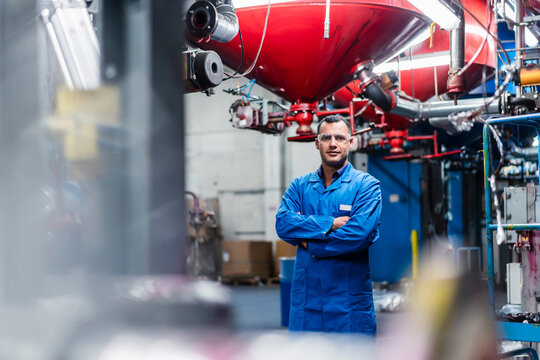 Confident male engineer in blue coat with arms crossed standing in factory