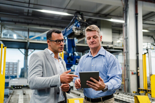 Mature manager and supervisor working on digital tablet in industry