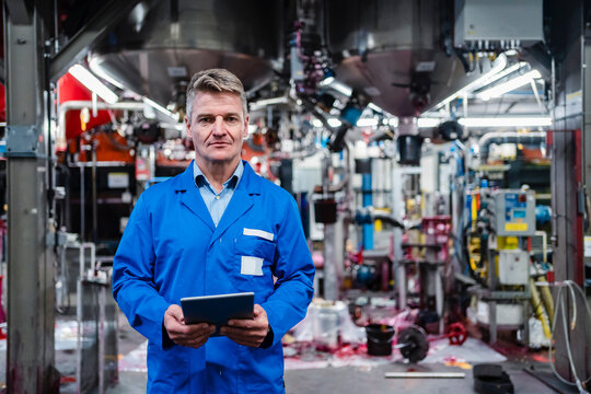 Mature engineer holding digital tablet while standing in industry