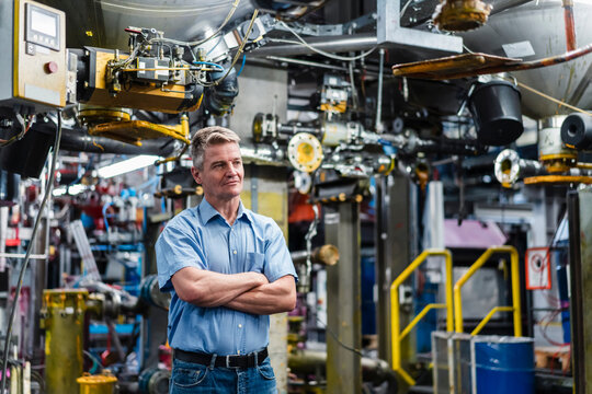 Male entrepreneur with arms crossed contemplating while standing against machinery in factory