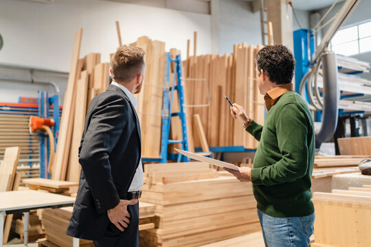 Two carpenters talking in front of stacked wood planks in production hall