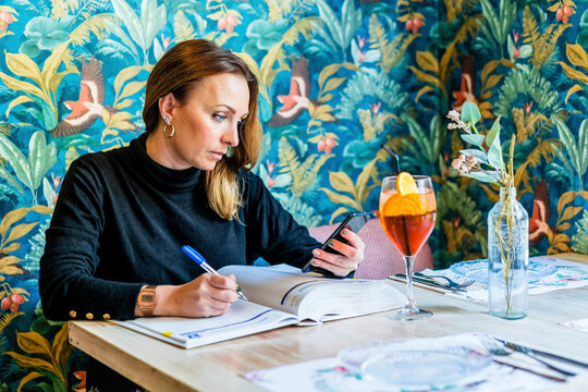 Portrait of adult woman working at restaurant table