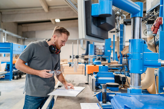 Portrait of carpenter inspecting machines in production hall