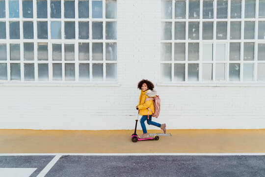 Portrait of carefree girl with curly hair riding push scooter on road by building in city
