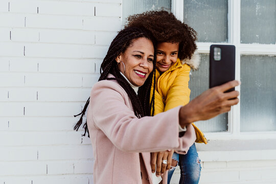Smiling mother taking selfie with daughter against wall