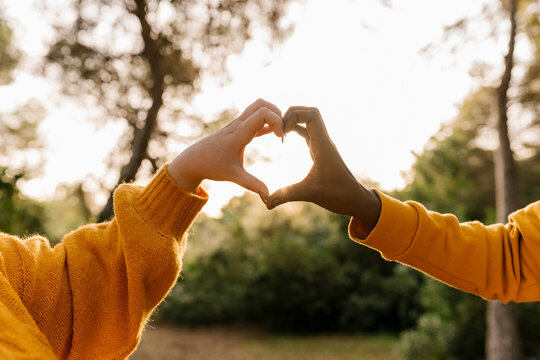 Couple making heart shape with hands during sunset at forest