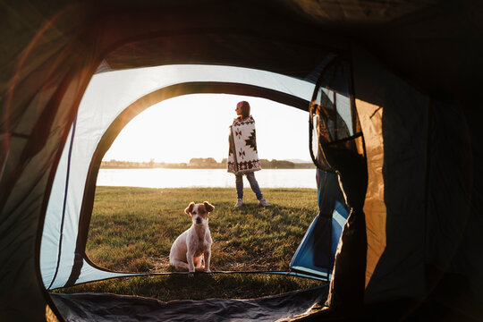 Woman wrapped in shawl camping with dog against lake seen through tent
