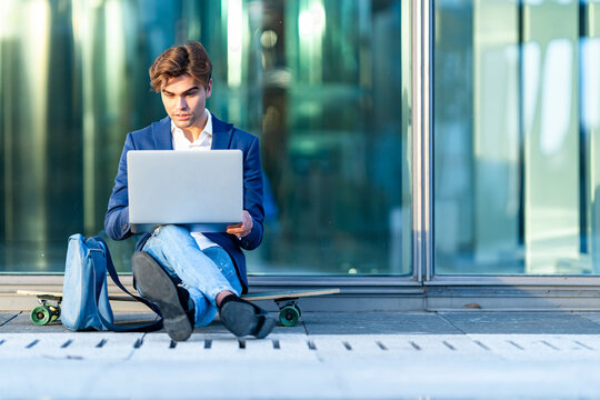 Male entrepreneur using laptop while sitting on skateboard against glass during sunny day