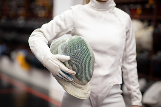 Woman in fencing outfit standing at gym