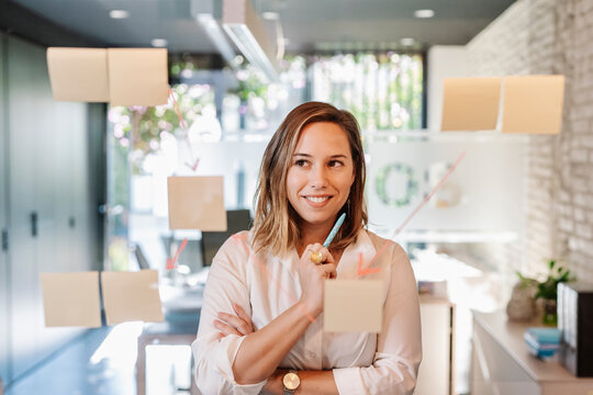 Smiling businesswoman looking at adhesive notes stuck on glass wall in office
