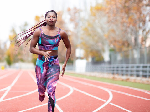 Young sportswoman wearing sports clothes running on track